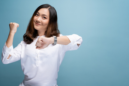Happy woman holding hand with wrist watch isolated on a blue background 版權商用圖片