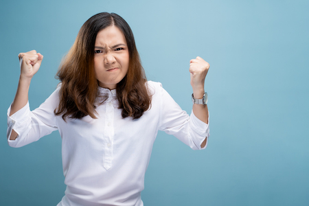 Angry woman screaming isolated over blue background