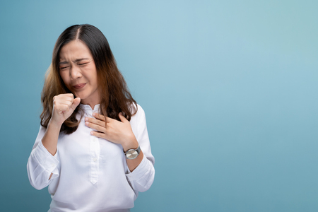 Woman has sore throat isolated over blue background Stock Photo