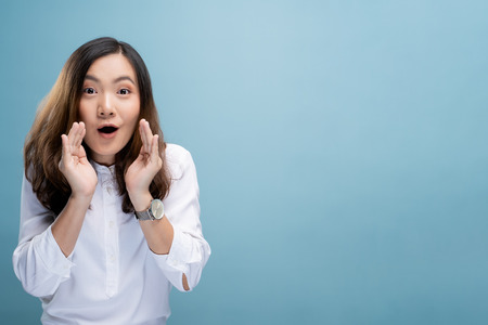 Woman make gossip gesture isolated over blue background