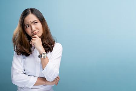 Vrouw voelt zich verward geïsoleerd over blauwe achtergrond Stockfoto