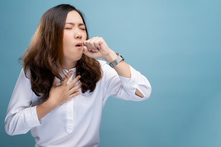 Woman has sore throat isolated over blue background Фото со стока