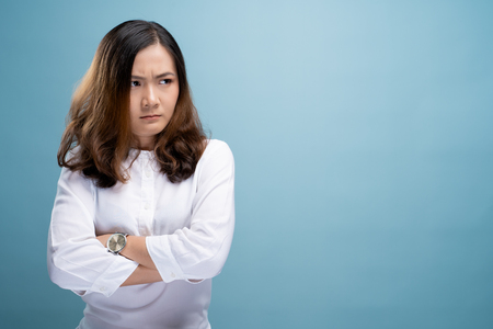 Angry woman standing isolated over blue background Stock Photo