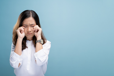 Sad woman crying and standing isolated on blue background 스톡 콘텐츠