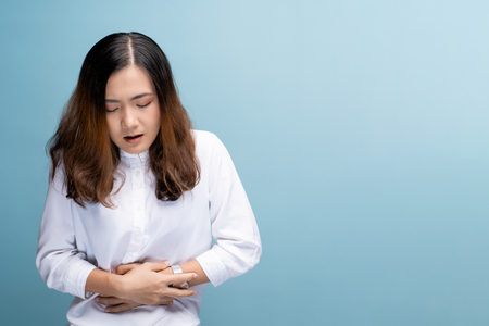 Woman has stomachache isolated over blue background