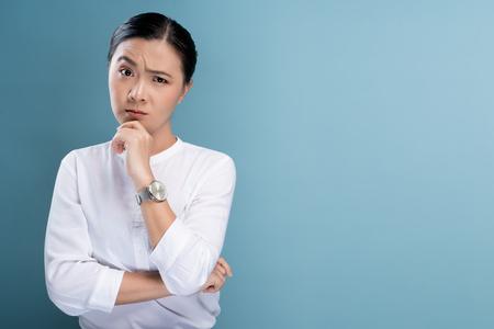 Frau fühlt sich verwirrt auf blauem Hintergrund isoliert