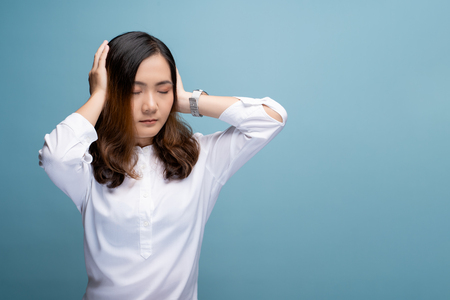Woman covering her ears and standing isolated over blue background Stock Photo