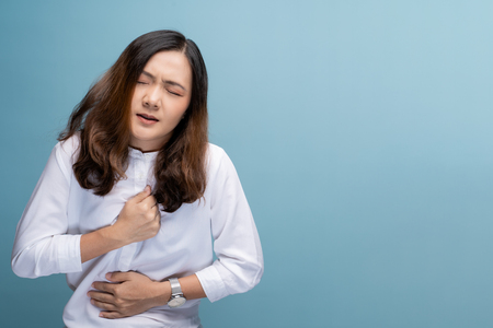 Woman has chest pain isolated over blue background
