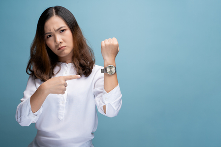 Angry woman pointing at her watch 版權商用圖片