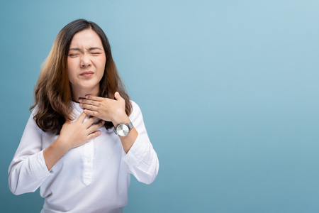 Woman has sore throat isolated over blue background Imagens