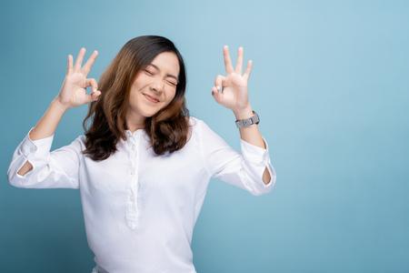 Gelukkige vrouw weergegeven: OK gebaar geïsoleerd op background Stockfoto