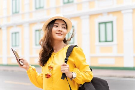 Happy tourist woman used smart phone for searching the street locations