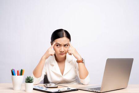 Porträt einer verwirrten Frau, die im Büro lokalisiert über dem Hintergrund sitzt