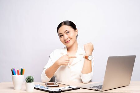 Happy woman holding hand with wrist watch at office isolated over background 스톡 콘텐츠