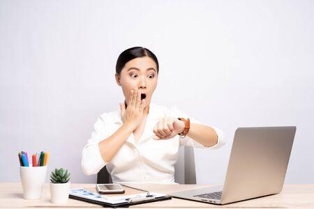 Donna scioccata che tiene la mano con l'orologio da polso in ufficio isolato su sfondo
