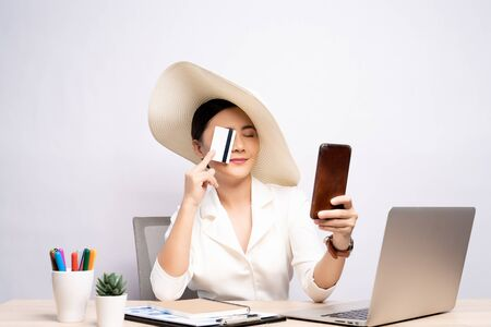 Woman wearing hat use smart phone and credit card at office isolated over background Stockfoto
