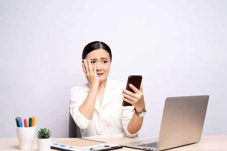 Woman looking at smartphone and feel scared at office isolated over background Stock Photo