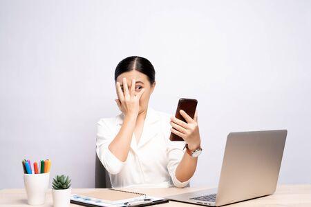 Frau, die auf Smartphone schaut und Angst im Büro hat, isoliert über Hintergrund Standard-Bild