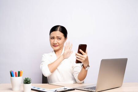 Woman looking at smartphone and feel scared at office isolated over background Archivio Fotografico