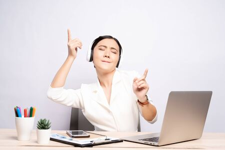 Frau mit Kopfhörern Musikhören im Büro über Hintergrund isoliert
