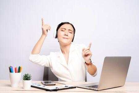 Kobieta ze słuchawkami słucha muzyki w biurze na białym tle nad tłem
