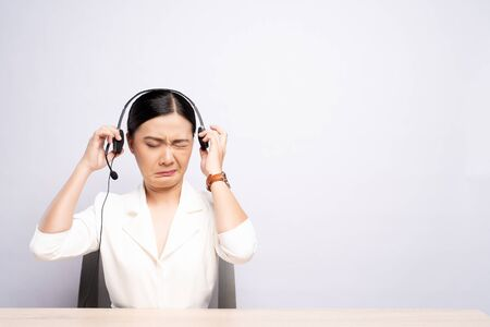 Woman operator in headset feel annoyed over white background 写真素材