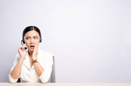 Woman operator in headset make whisper gesture over white background