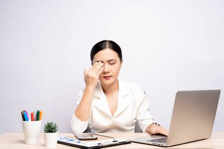 Woman has eyes pain at office isolated over white background