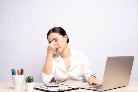 La mujer tiene dolor en los ojos en la oficina aislada sobre fondo blanco.