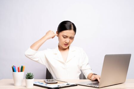 Woman putting a finger into her ear at office isolated white background