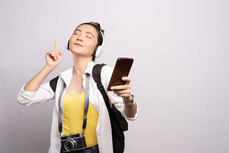 Tourist woman listening music from smartphone isolated over white background