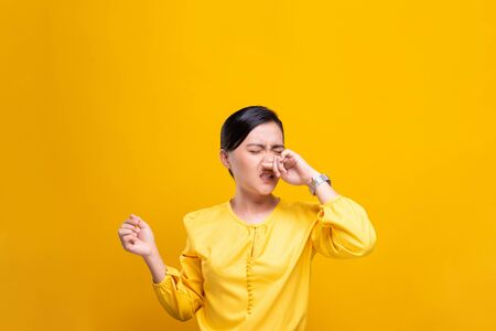 Woman wipe her nose and standing isolated over background