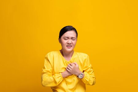 Woman has chest pain isolated over yellow background