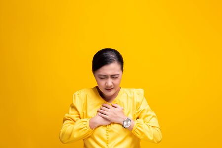 Woman has stomach ache isolated over yellow background