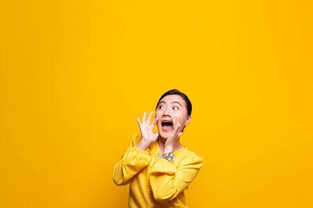 Glückliche Frau, die Schreigeste lokalisiert über gelbem Hintergrund macht Standard-Bild