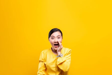 Woman make gossip gesture isolated over yellow background Stockfoto - 130285304