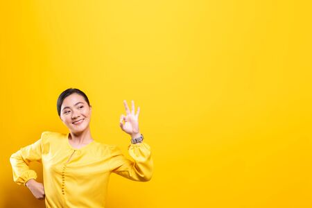 Happy woman showing OK gesture isolated on background
