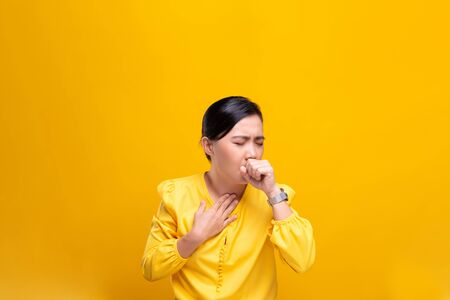 Woman has sore throat isolated over yellow background Banque d'images