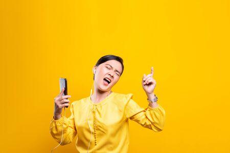 Frau mit Kopfhörern, die Musik vom Smartphone auf isoliertem gelbem Hintergrund hört