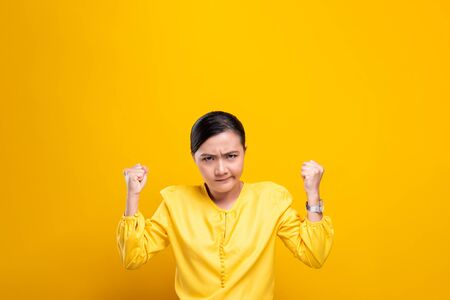 Angry woman standing isolated over yellow background