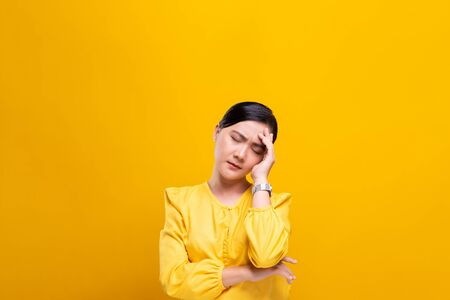 Woman has headache isolated over yellow background Archivio Fotografico - 130285375