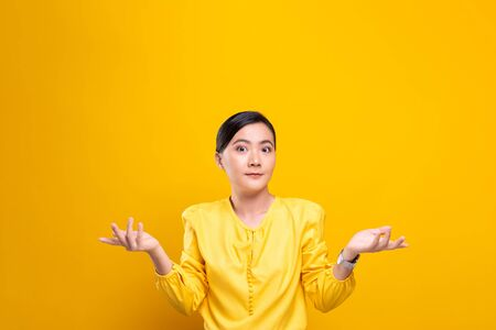 Woman feel confused isolated over yellow background Archivio Fotografico