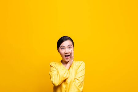 Woman make gossip gesture isolated over yellow background Stockfoto - 130285430