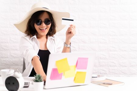 Happy woman wearing hat and sunglasses use laptop and credit card at office