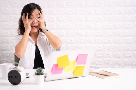 Woman sitting at home office working using computer laptop and shocking and scared something