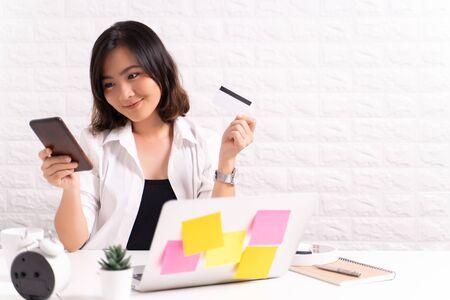 Mujer feliz usa teléfonos inteligentes y tarjetas de crédito en la oficina Foto de archivo