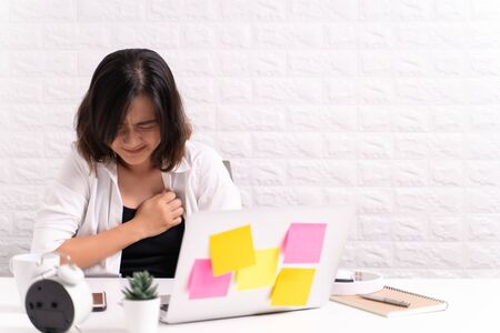 Woman has chest pain at office Stock Photo
