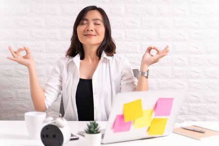Donna che medita tenendo le mani in gesto di yoga in ufficio