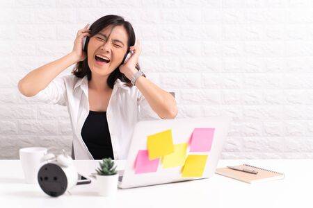 Happy woman with headphones listening music at office