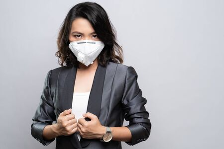 Businesswoman wearing the N95 mask isolated over white background